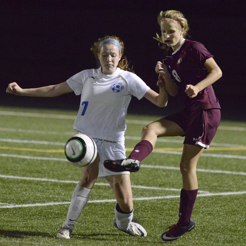 Kate Breed of Cape Elizabeth, right, kicks the ball past Emma England of Falmouth during their Western Maine Conference game at Falmouth High.