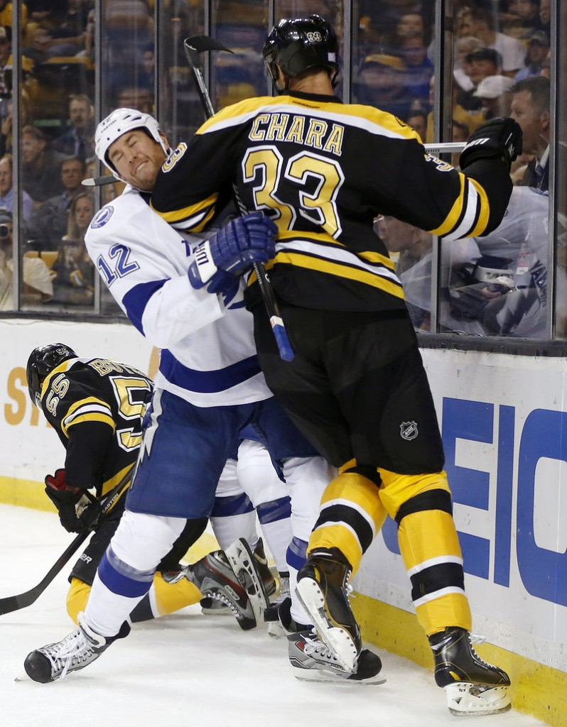 Boston defenseman Zdeno Chara towers over Tampa Bay's Ryan Malone during first-period action of Thursday night's season opener in Boston, won by the defending conference champion Bruins.