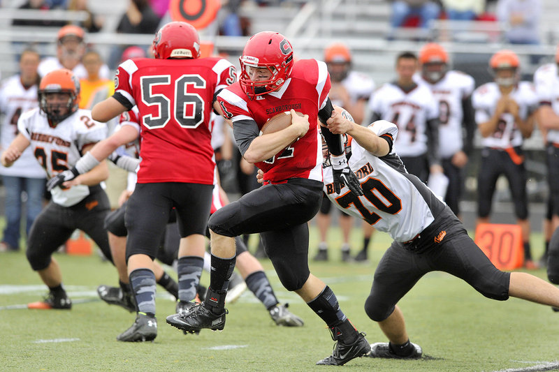 Scarborough quarterback Ben Greenberg pulls away from Peter Lekakos of Biddeford and scampers for a first down Saturday during Scarborough's 41-21 victory at home.