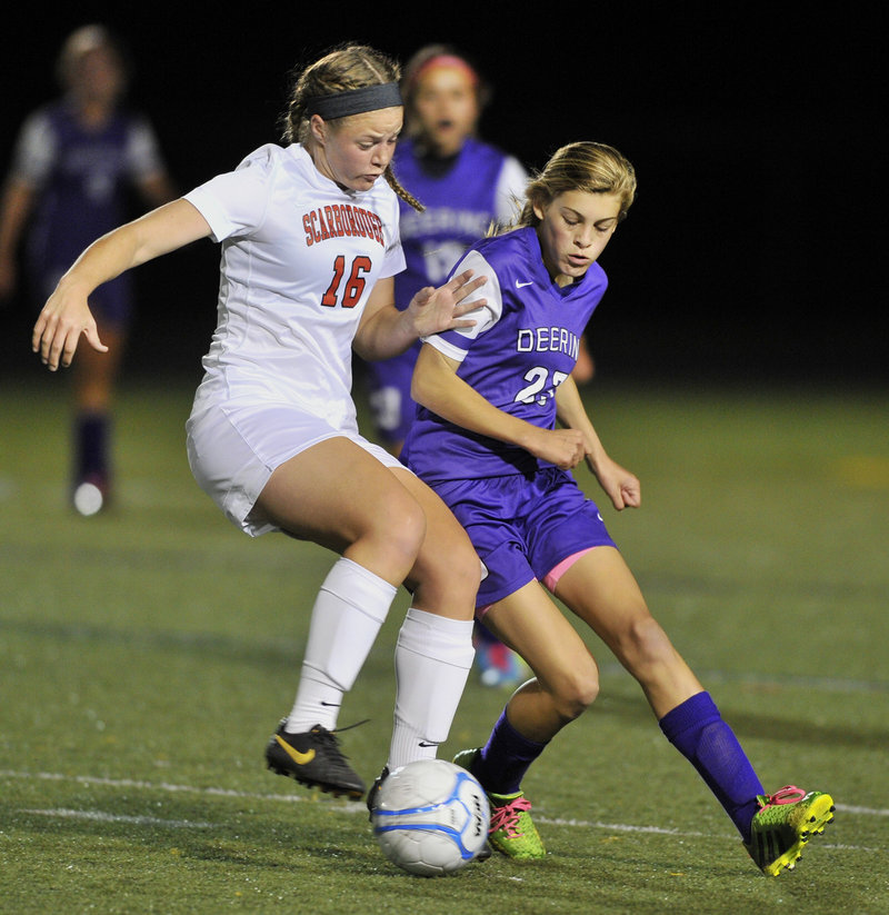 Sam Sparda, left, attempts to dribble around Ewka Varney of Deering. Scarborough, the defending state champion, improved to 9-0-1. Deering is 7-3.