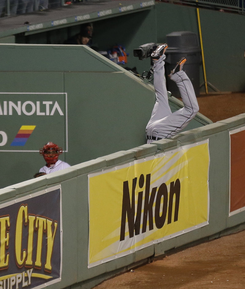 Tigers right fielder Torii Hunter flips over the wall into the Red Sox bullpen after his valiant bid to catch David Ortiz's grand slam was just a little too late.