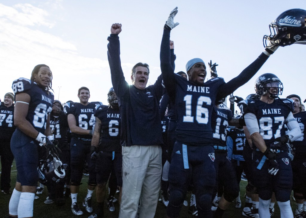 Coach Jack Cosgrove celebrates with his players after UMaine toppled Rhode Island 41-0 on Saturday to capture the CAA regular-season championship.