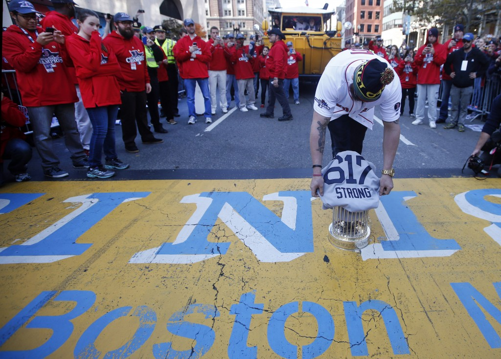 Boston Red Sox's Jonny Gomes places the championship trophy and a Red Sox baseball jersey at the Boston Marathon finish line during a pause in their World Series victory rolling rally in Boston on Saturday to remember those affected by the Marathon bombing.