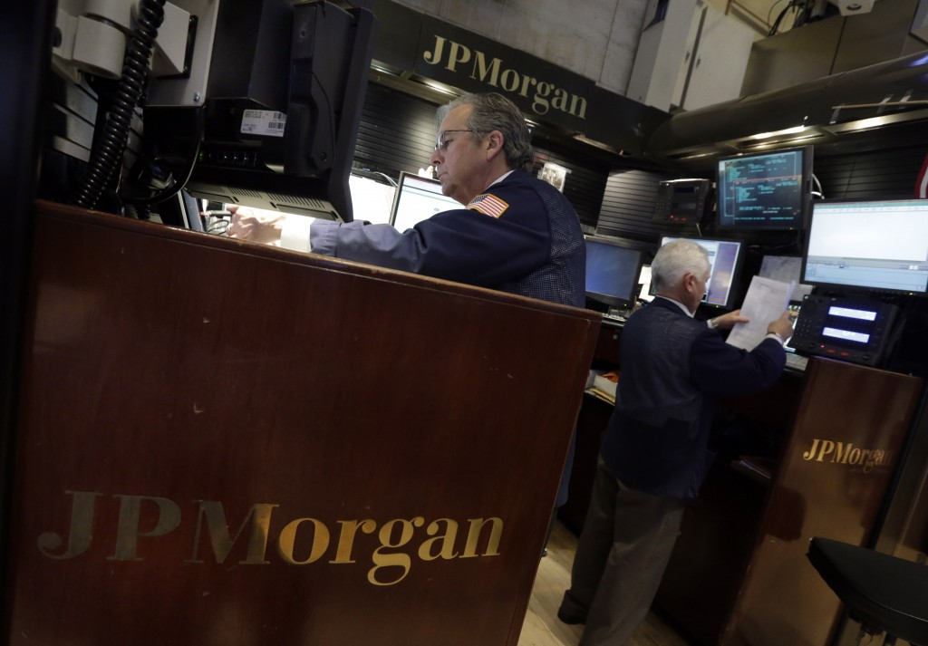 A pair of traders work in the JPMorgan booth on the floor of the New York Stock Exchange on Tuesday. The $13 billion settlement amount is only about half of JPMorgan's record 2012 net income of $21.3 billion, which made it one of the most profitable U.S. banks last year.