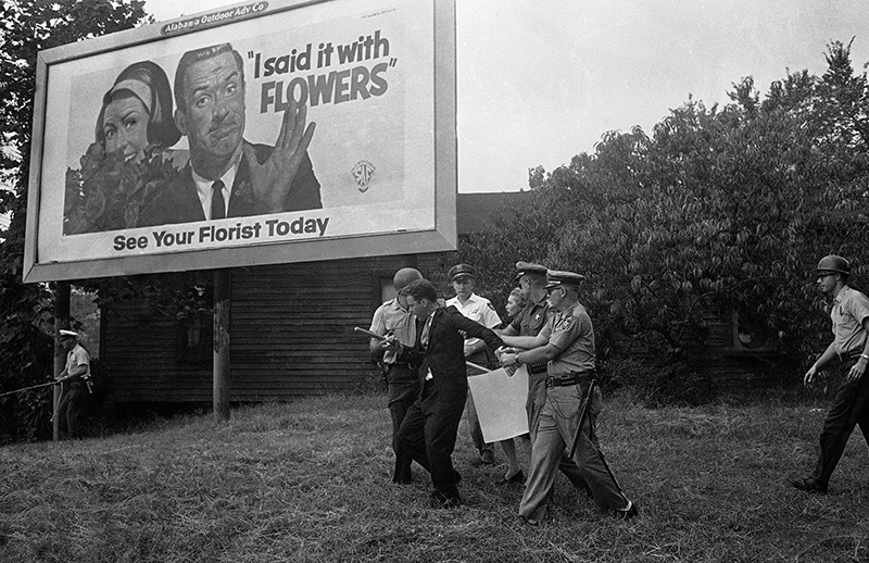 In this Sept. 4, 1963 file photo, police wrestle with an unidentified white man near a billboard after a demonstration at the newly-integrated Graymont Elementary School in Birmingham, Ala. On Duty Officer Standing Looking Away