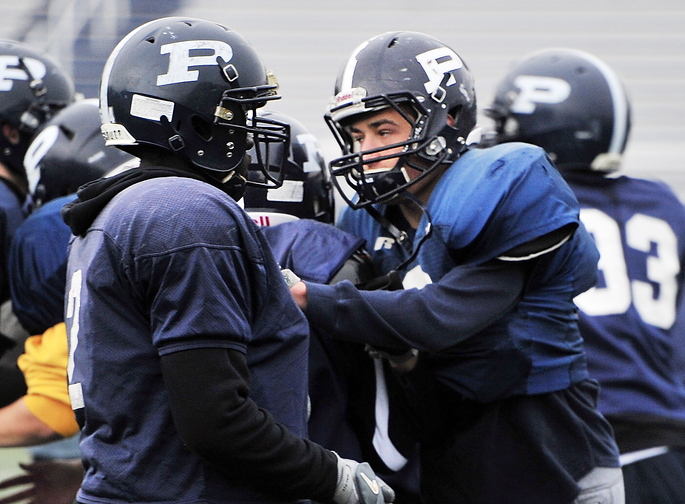 Football players, Justin Zukowski and Joe Esposito are cousins and linebackers for Portland High School and will play in the annual Thanksgiving Day football match against Deering High School. Here, Joe Esposito, right, blocks during a practice play.