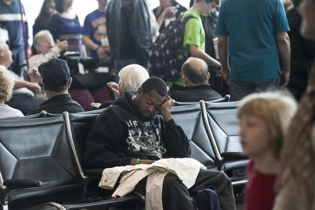 Rashad Simmons of Tampa naps while waiting for his flight at Tampa International Airport on Tuesday in Tampa, Fla. Travelers are facing delays due to winter storms in other areas of the country.
