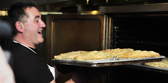Stuart Leckie, manager of the food service program at St. Joseph's College and coordinator of the annual bake-off, rejoices at the first batch of baked apple pies on Wednesday.