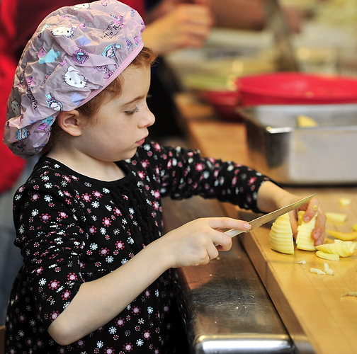Virginia March, 8, slices apples for the pies at the bake-off at St. Joseph's College in Standish. The college food pantry was giving 225 families food baskets, each containing a hot pie.