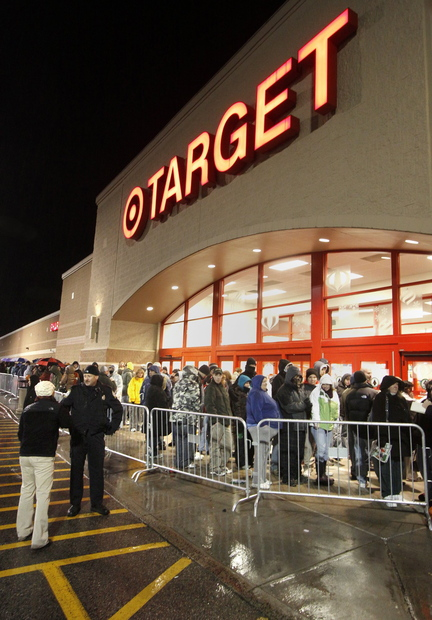 Shoppers wait outside Target in South Portland before the store opened early on Black Friday in 2010. Target, Walmart and Kohl's are among more than two dozen major chains that have lowered their profit outlooks.