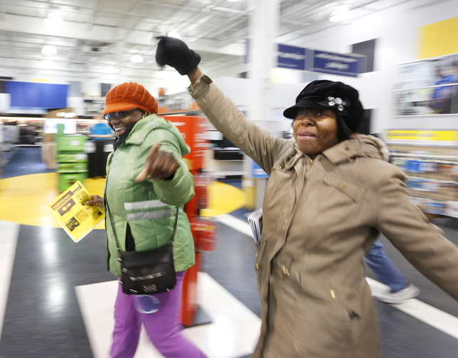 Black Friday shoppers Paulette Darby of South Portland, left, and Annmarie Warburton of Portland, hit the floor running after being among the first to enter Best Buy in South Portland at midnight on Friday.
