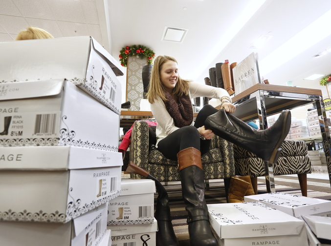 Emily Doyon, 18, of Biddeford tries on a few pairs of boots, shortly after midnight on Friday while shopping with her mother at Bon-Ton in South Portland. Many stores were open early for Black Friday shopping.