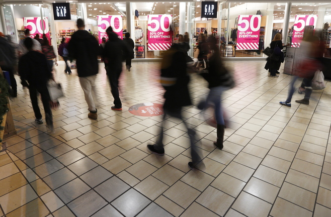 Black Friday shoppers shuffle past a window advertising a sale shortly after midnight on Friday at the Maine Mall.