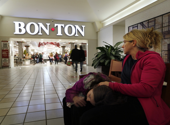 Zoe Sweet of Westbrook rests with her daughter, Luci, 10, as she waits for another daughter and her friend to finish shopping at Bon-Ton in South Portland. The Maine Mall and many of the surrounding stores opened their doors at around midnight to accomodate Black Friday shoppers.
