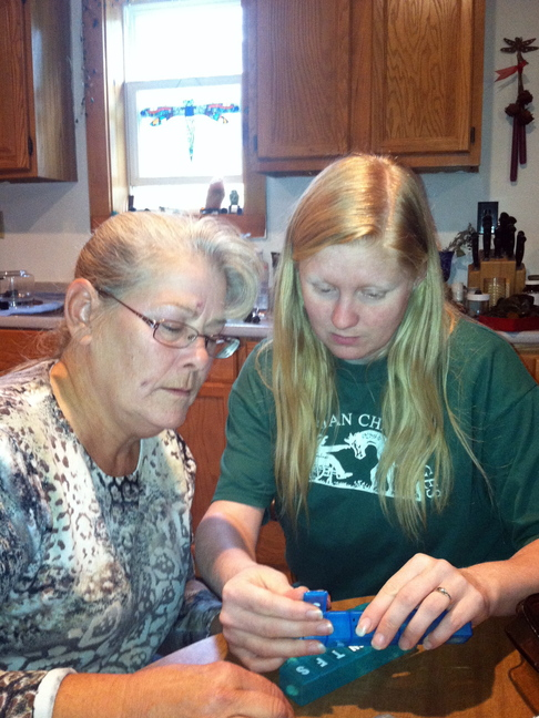 Amanda Sheppard, right. helps Anette Adams organize her pills at Adams' home in New Haven, Vt.
