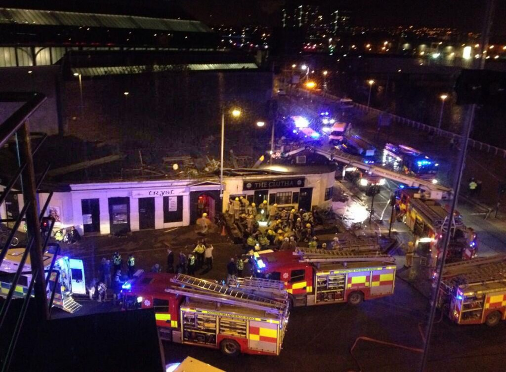 Police and Scottish Fire and Rescue services at the scene Saturday, Nov. 30, 2013, following the helicopter crash at the Clutha Bar in Glasgow, Scotland. Scottish emergency workers were sifting through wreckage Saturday for survivors of a police helicopter crash onto a crowded Glasgow pub that has killed at least one person and injured more than two dozen. The Clutha pub, near the banks of the River Clyde, was packed Friday night and a ska band was in full swing when the chopper slammed through the roof. The number of fatalities is expected to rise, officials said.