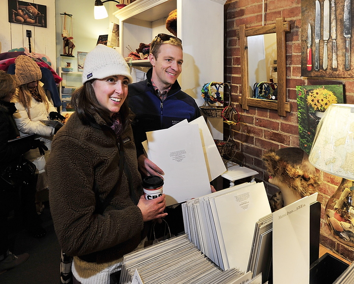 """Julie and Toby Walch of Scarborough look at photographs at Lisa-Marie's Made in Maine on Exchange Street in Portland on Saturday. """"It's what tourists want. They don't want something made in China,"""" said Marie Stewart, the store manager."""
