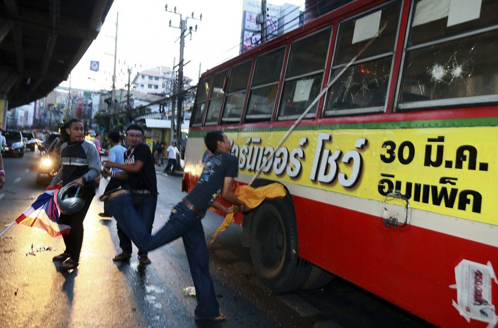 Anti-government protesters attack people they suspected of supporting the current Thai government on the bus in Bangkok,Thailand Saturday, Nov. 30, 2013. A mob of anti-government protesters smashed the windows of a moving Bangkok bus Saturday in the first eruption of violence after a week of tense street protests.