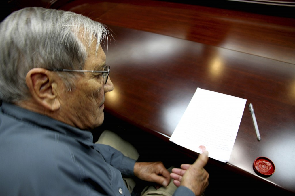 In this Nov. 9, 2013 photo released by the Korean Central News Agency (KCNA) and distributed Nov. 30, 2013 by the Korea News Service, U.S. citizen Merrill Newman, 85, applies his thumb print to a document which North Korean authorities say was an apology which Newman wrote and read in North Korea. Newman, an avid traveler and retired finance executive, was taken off a plane Oct. 26 by North Korean authorities while preparing to leave the country after a 10-day tour.