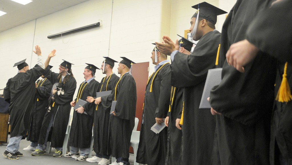 Maine State Prison inmates congratulate each other Monday after receiving diplomas at the Warren prison from the University of Maine at Augusta.