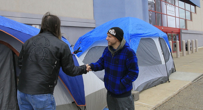 Campers Tony Avitar, left, and Jonas Allooh greet each other Tuesday at their tents outside of a Best Buy store in Cuyahoga Falls, Ohio, as they hope to be among the first through the doors to score Black Friday shopping bargains.