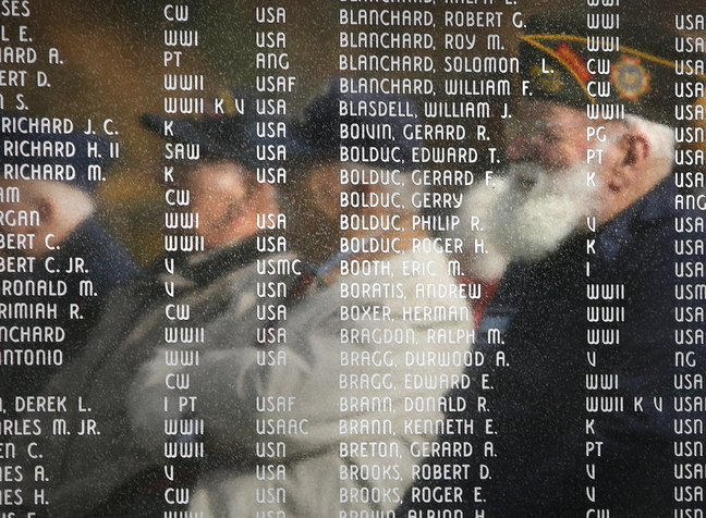 John Ames of Cumberland, right, and fellow Korean War veterans are reflected in the war monument at Moss Side Cemetery in Cumberland during a Veterans Day ceremony Monday. Korean War veterans traveled to locations in Cumberland, North Yarmouth and Yarmouth.
