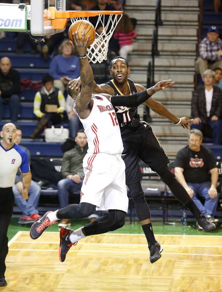 Despite the visual impairment from Erie's of C.J. Leslie, Maine's Jermaine Taylor scores during the second quarter of Sunday's game at the Portland Expo. Taylor went down in the second half with what could be a serious injury to his left knee.