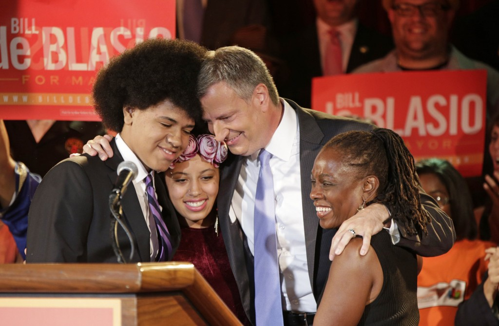 New York mayoral candidate Bill de Blasio embraces his son Dante, left, daughter Chiara, second from left, and wife Chirlane McCray. Bill de Blasio is apparently the first white politician in U.S. history elected to a major office with a black spouse by his side.