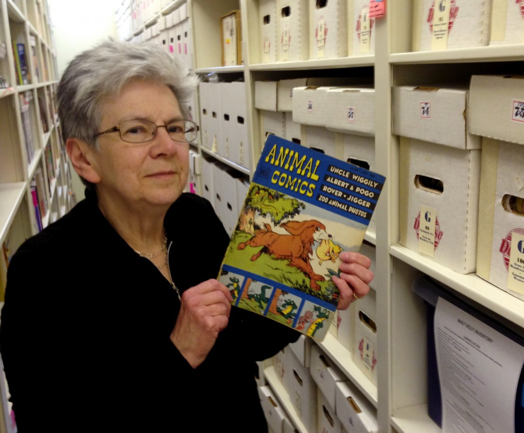 """Maggie Thompson shows off a copy of """"Animal Comics"""" in the addition built onto her Wisconsin home to house her estimated tens of thousands of comic books."""