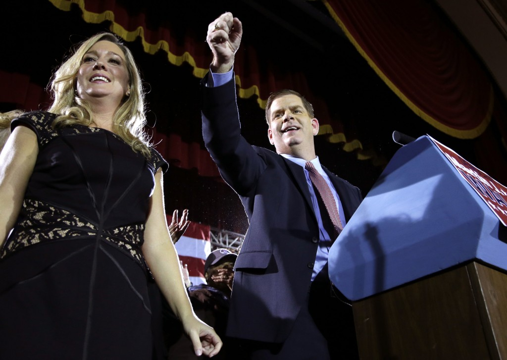 Newly elected Boston Mayor Martin Walsh, right, gestures to the crowd as his girlfriend Lorrie Higgins, left, looks on during a watch party Tuesday, Nov. 5, 2013 in Boston. Walsh defeated Boston City Councilor John Connolly in the mayoral race. Thomas Menino, the city's longest serving mayor, announced earlier this year he would not seek another term after more than two decades in office.