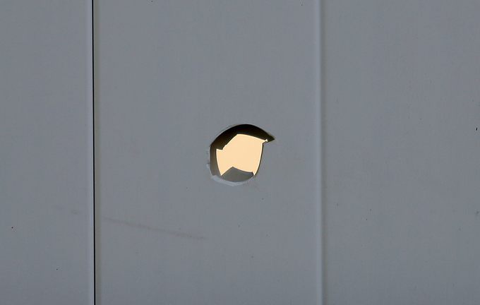 A hole, which Toni Macquinn said was caused Wednesday by a stray bullet from a hunter's rifle, is visible in her backyard fence in Old Orchard Beach.