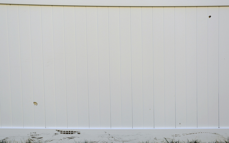 """Two bullet holes, at bottom left and top right, are visible in Toni Macquinn's fence at her home off Cascade Road in Old Orchard Beach on Wednesday. """"I could have been seriously hurt or killed,"""" she said."""