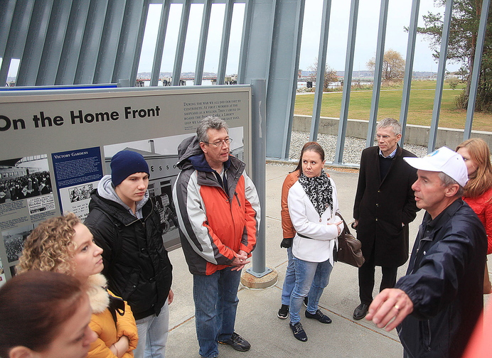 Andrei Strukov, center, an interpreter from Fairfield, listens with a Russian delegation from Portland's sister city of Archangel as Portland City Councilor Ed Suslovic, far right, explains the history behind the Liberty Ship Memorial at Bug Light Park during a tour in South Portland on Sunday.