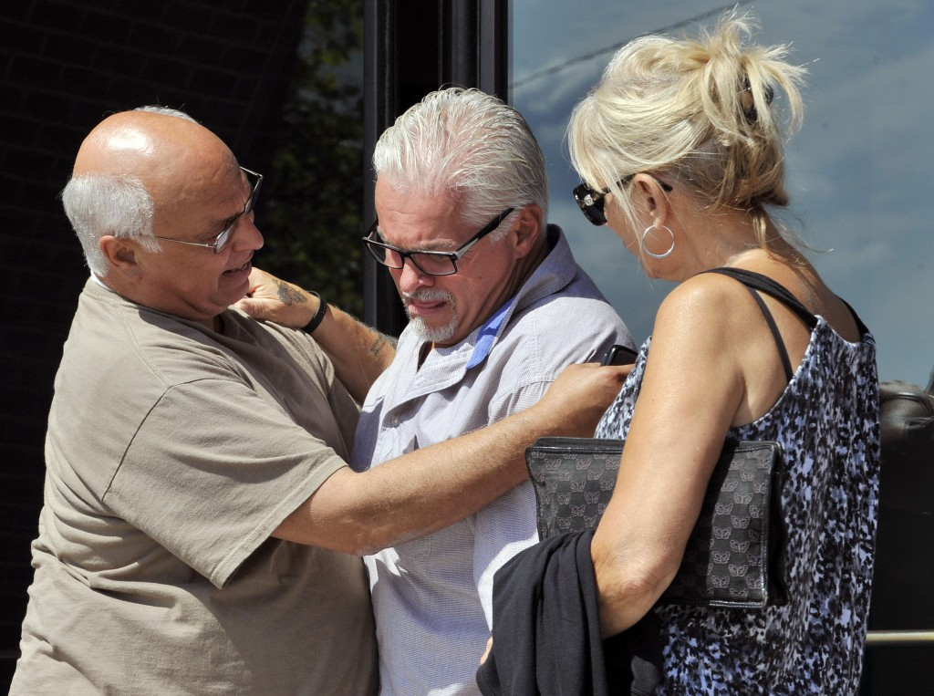 """Steven Davis, brother of slain Debra Davis, center, is comforted by Skip Marcella, left, on Aug. 12, after speaking outside federal court in Boston where a jury found James """"Whitey"""" Bulger guilty on several counts of murder, racketeering and conspiracy. Jurors could not agree whether Bulger was involved in Debra Davis' killing. When Bulger is sentenced this week, family members of eight slaying victims are hoping a judge will let them speak, even though Bulger was acquitted in those deaths."""