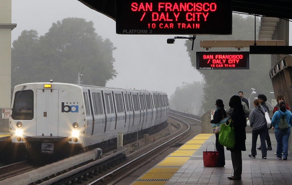 In this Oct. 22, 2013, file photo, Bay Area Rapid Transit (BART) passengers wait for a train in Oakland, Calif. A BART labor union overwhelmingly ratified a contract agreement on Friday after a bitter dispute prompted two San Francisco area strikes, officials said.