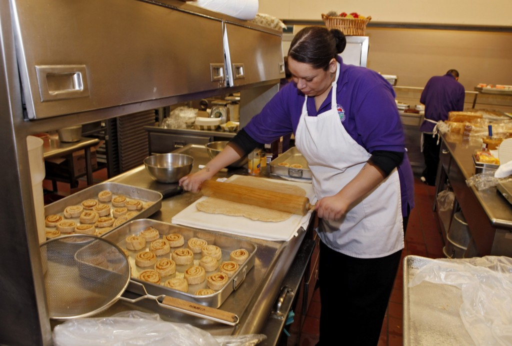 Alexes Garcia makes cinnamon rolls for students' lunches in the kitchen at Kepner Middle School in Denver. The rolls are made using apple sauce instead of trans fats.