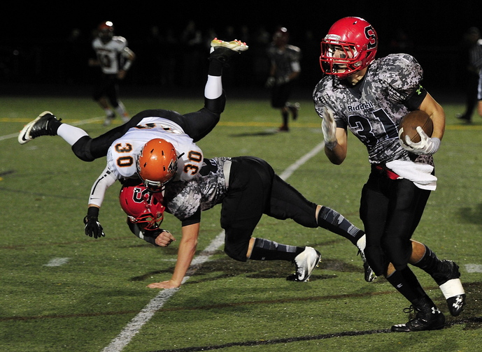 Scarborough's Dan LeClair gets good blocking from teammate Zachary Carriero as he heads downfield for a touchdown. Thwarted in his attempt to make a tackle is Biddeford's Nate Ouellette.