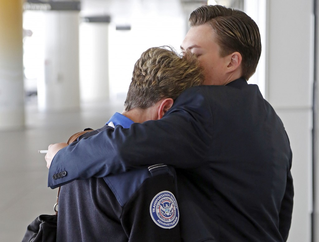 Transportation Security Administration employees hug outside Terminal 1 at Los Angeles International Airport on Friday after a gunman armed with a semi-automatic rifle killed a TSA employee and wounded two other people. Flights were disrupted nationwide.