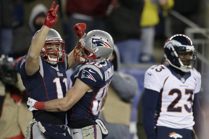 Patriots wide receiver Julian Edelman, left, celebrates his touchdown catch with Danny Amendola, center, as Denver Broncos cornerback Quentin Jammer walks by in the third quarter Sunday in Foxborough, Mass.