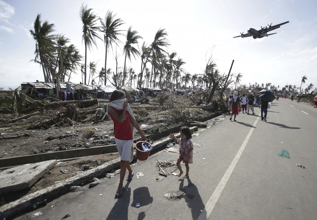 Survivors look up at a military C-130 plane as it arrives at typhoon-ravaged Tacloban city, Leyte province, in central Philippines on Monday. Stunned survivors of one of the most powerful typhoons ever to make landfall picked through the remains of their homes Monday and pleaded for food and medicine as the Philippines struggled to deal with what is likely its deadliest natural disaster.