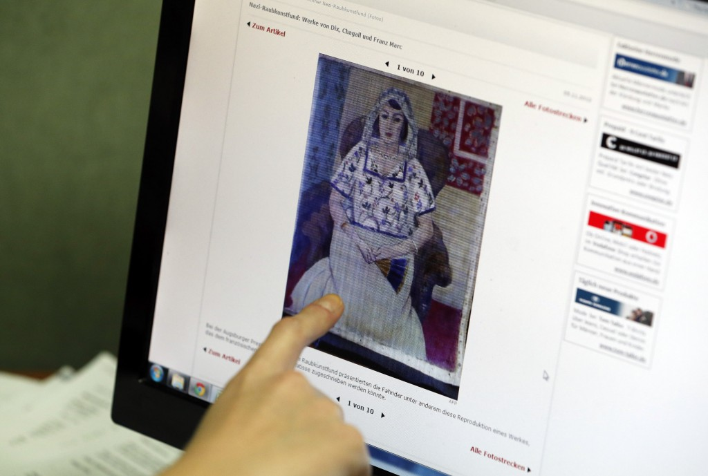"""A researcher for the Art Loss Register in London points to a picture on a news website showing a painting by Henry Matisse titled """"Sitting Woman,"""" which is part of the art recently found in Munich, Germany."""