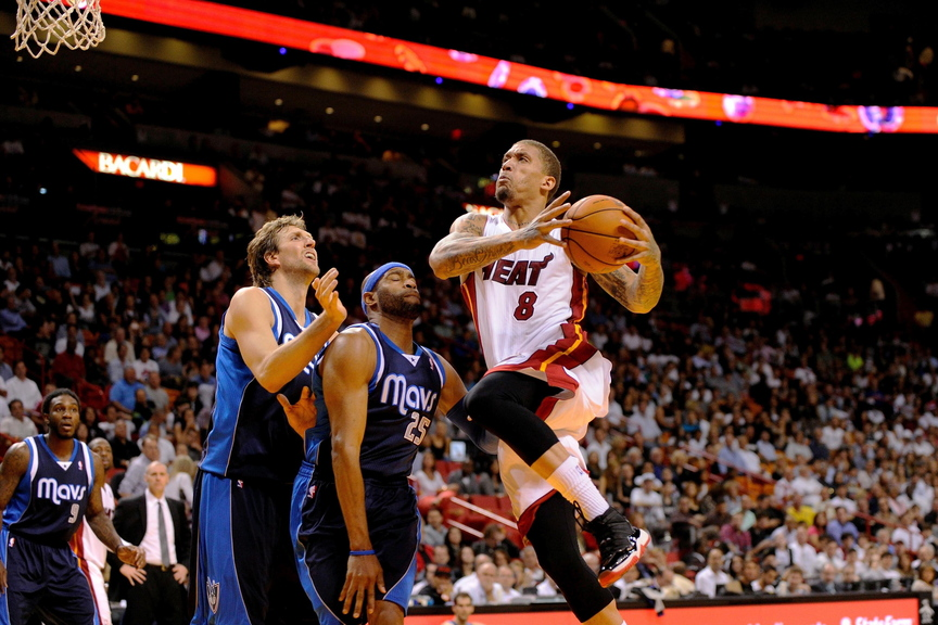 Miami's Michael Beasley drives to the basket as Dallas' Dirk Nowitzki (far left) and Vince Carter look on during the Heat's 110-104 win Friday.