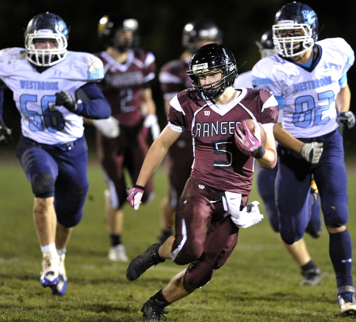 Greely's Sam Peck gets into the Westbrook secondary for some yardage as Westbrook's Alex Gauvin (66) and Noah Collins (82) give chase during first half action Friday night.