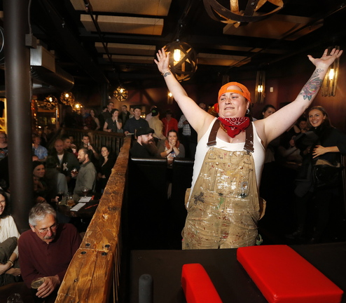 Kate Squibb, also known as Lumber Smack Sally, celebrates her first-round victory over Barrel Roll Barbie during an arm wrestling fundraiser Thursday at In'finiti.