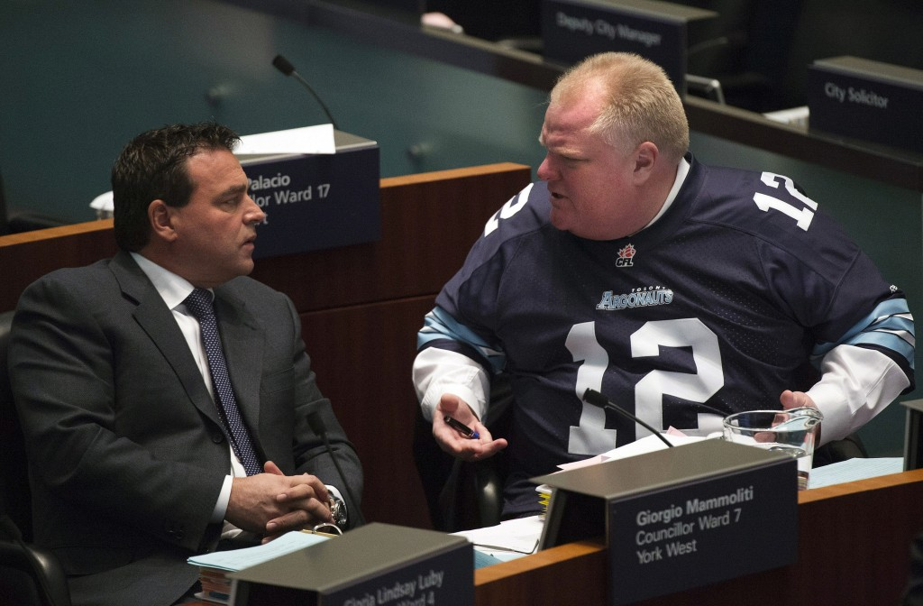 Mayor Rob Ford has a conversation with Councillor Giorgio Mammoliti at city hall in Toronto on Thursday. Ford is threatening to take legal action against former aides who told police of their concerns about his drug use and drunken driving.