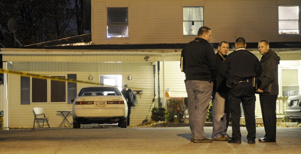 Augusta and state police detectives confer Wednesday evening outside an apartment at 32 Crosby St. in Augusta after a woman was found dead and a man wounded in the first-floor unit just after 8 p.m.