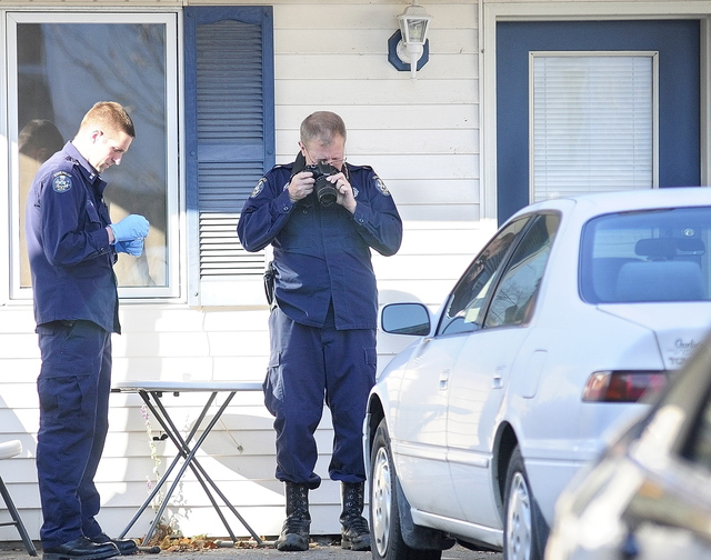 Investigators work at the scene of a homicide Thursday at 32 Crosby St. in Augusta.