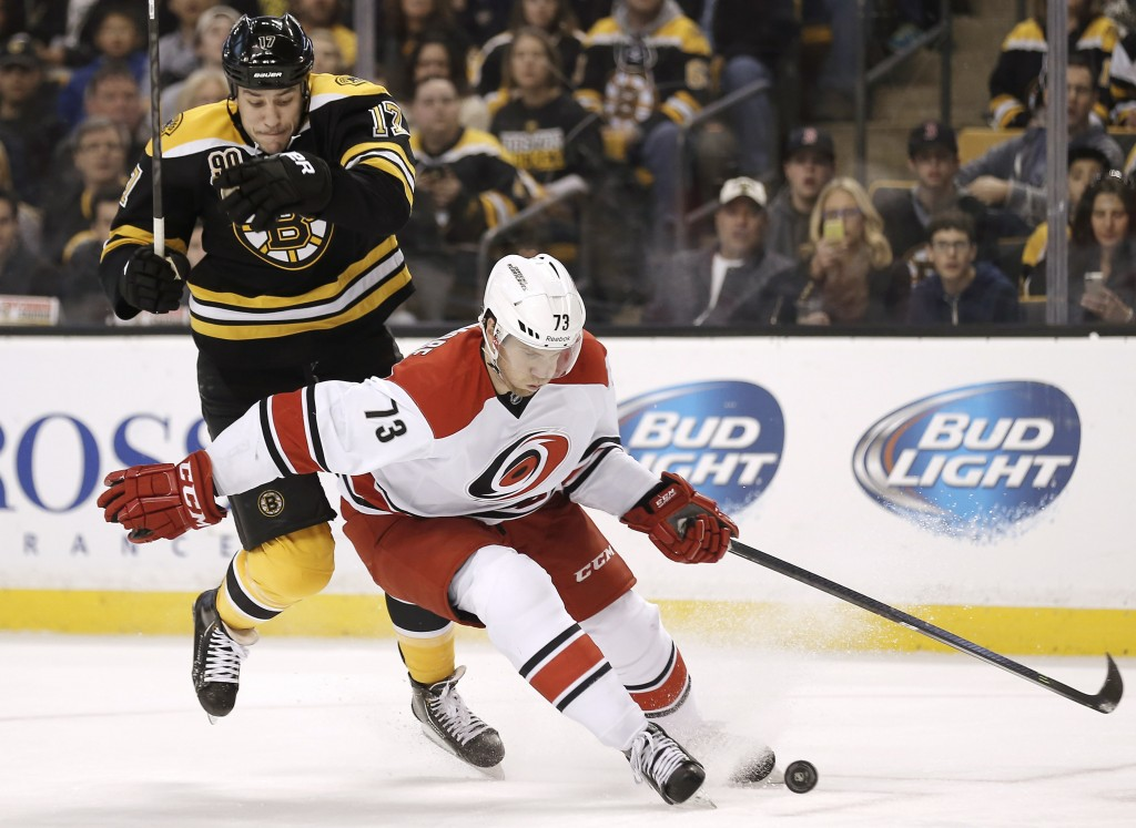 Brett Bellemore of Carolina tries to hold back Boston's Milan Lucic in the second period Saturday in Boston. The Bruins won in OT, 3-2.