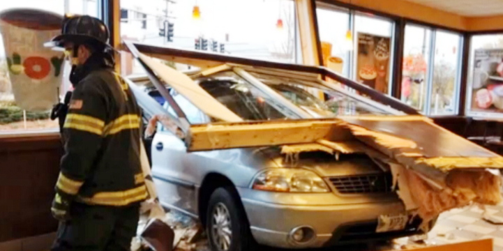 A firefighter surveys the damage after a minivan crashed into the Dunkin' Donuts at Woodfords Corner.