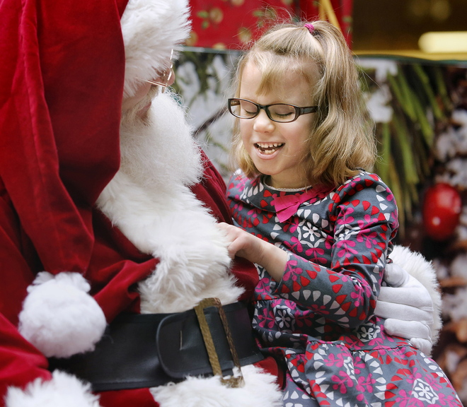 Isabella Sherman, 6, of Saco smiles as she visits with Santa on Sunday at the Maine Mall during a special experience for children with autism. Lights were dimmed and the traditional mall music shut off to limit distractions for the children and their families.